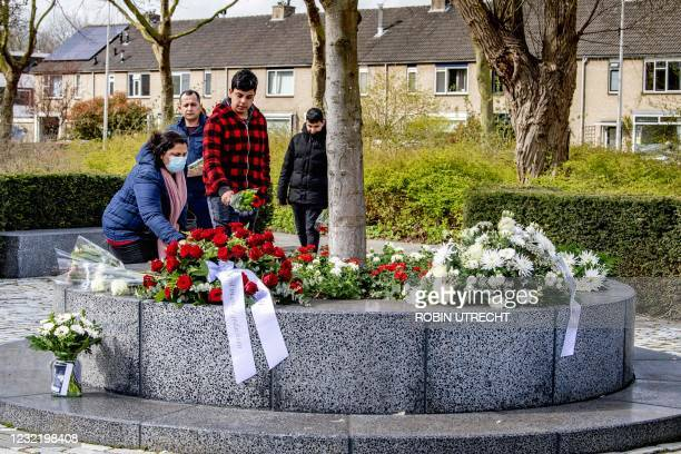 People lay flowers at a memorial for those killed at the Ridderhof shopping center in 2011, some 33 kilometers southwest of Amsterdam, on April 9,...