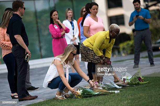 People lay flowers at the Dr Phillips Center for the Performing Arts in honor of the victims of the shooting at Pulse Nightclub June 13 2016 in...