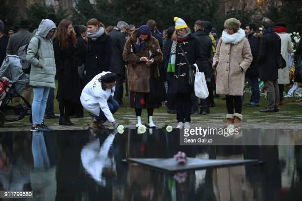 People lay flowers at the Memorial to the Sinti and Roma Victims of National Socialism following a commemoration ceremony on January 29 2018 in...