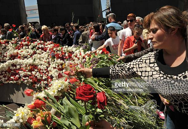 People lay flowers at the monument to Armenians killed by Ottoman Turks during World War I in Yerevan on April 24 to mark the 99th anniversary of the...