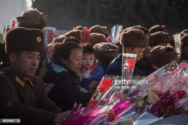 People lay flowers before a statue of late North Korean leader Kim JongIl to mark the sixth anniversary of his death at Mansu hill in Pyongyang on...