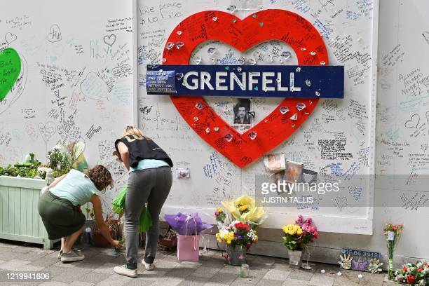 People lay flowers beside a wall where messages of support have been written surrounding Grenfell tower in west London on June 14 on the third...