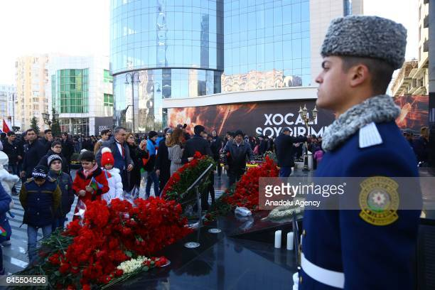 People lay flowers during the 25th anniversary of Khojaly Massacre at Ana feryadi monument in Baku Azerbaijan on February 26 2017 The massacre on...