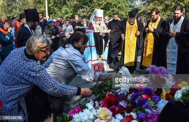 TOPSHOT People lay flowers for the victims during a church service in Kerch Crimea on October 18 after a student opened fire at a technical college...