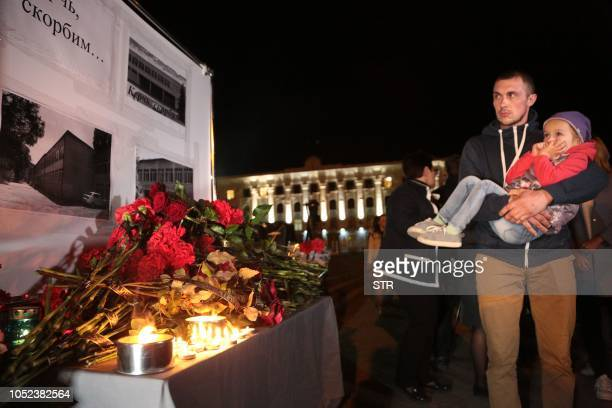 People lay flowers in downtown Simferopol Crimea on October 17 after nineteen people were killed and dozens more wounded most of them teenagers after...
