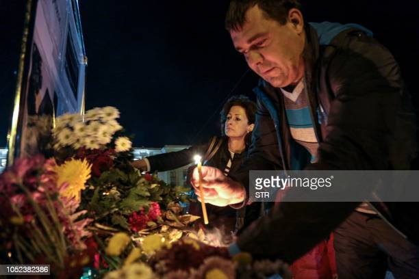 People lay flowers in downtown Simferopol on October 17 after nineteen people were killed and dozens more wounded most of them teenagers after a...