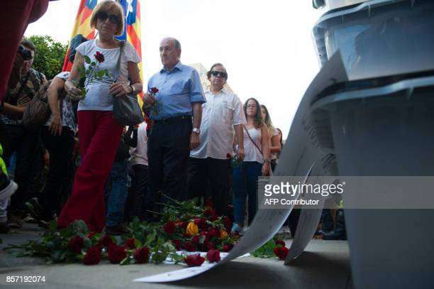 People lay flowers in front of ballot boxes used during the Catalan independence referendum in Pineda de Mar on October 3 during a general strike in...