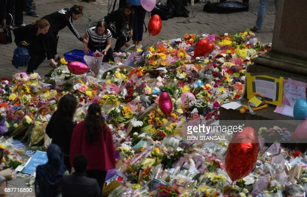 People lay flowers in St Ann's Square after relocating them from Albert Square in Manchester northwest England on May 24 placed in tribute to the...