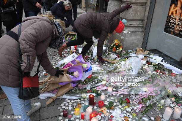 People lay flowers in tribute to the victims of Cherif Chekatt on December 14 2018 at Strasbourg's Christmas market one day after after French police...