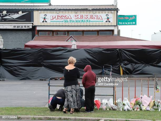 People lay flowers in tribute to the victims on the scene of a car crash into a pizza restaurant in SeptSorts 55km east of Paris on August 15...