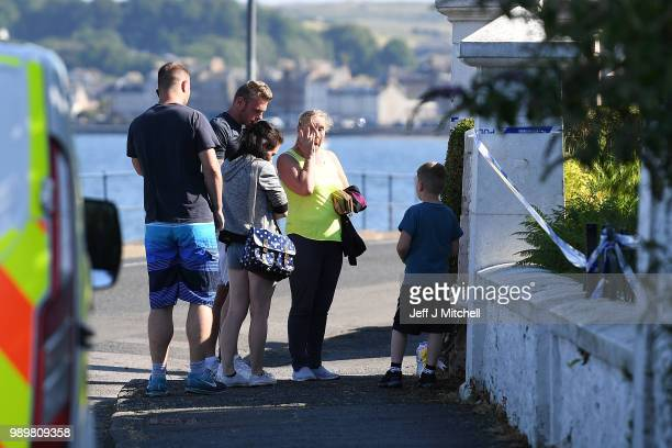 People lay flowers next to a cordoned of house on Ardbeg Road near to where the body of a six year old girl was found on July 2 2018 in Bute Scotland...