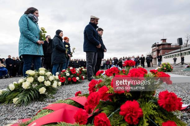 People lay flowers on a commemorative plaque during a ceremony at the memorial site of the former Nazi concentration camp Buchenwald near Weimar...