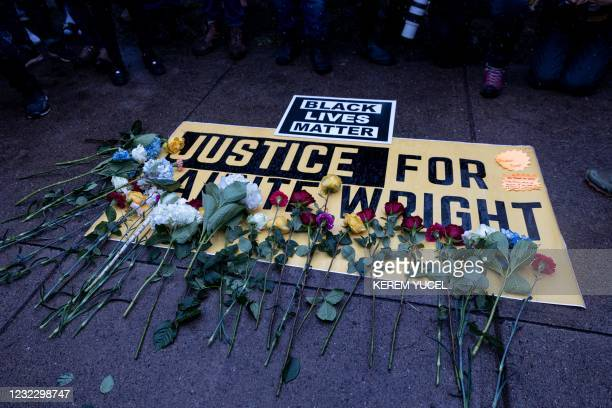 People lay flowers on a sign as they rally outside the Brooklyn Center police station to protest the death of Daunte Wright who was shot and killed...