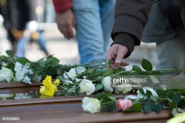 People lay flowers on the coffins of 26 teenage migrant girls found dead in the Mediterranean in early November during the inter religious funeral...