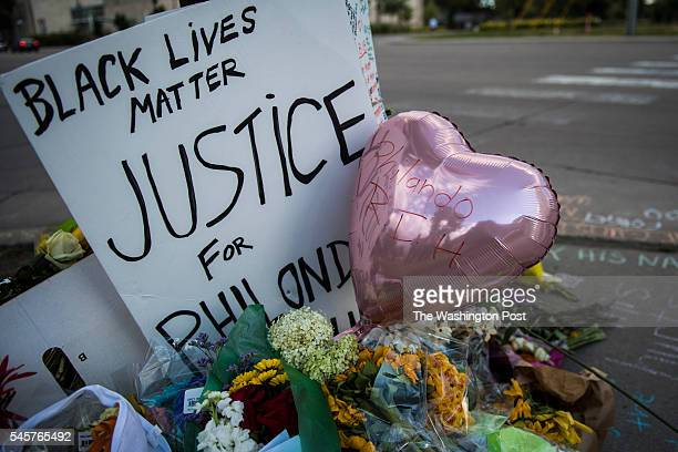 People lay flowers, write messages in chalk, and morn the death of Philando Castile near where he was fatally shot in Falcon Heights, Minn. On Friday...