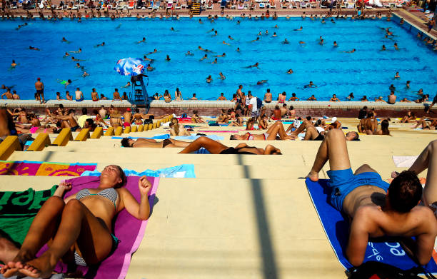 People Lay In The Sun At A Public Swimming Pool Belgrade On August 5