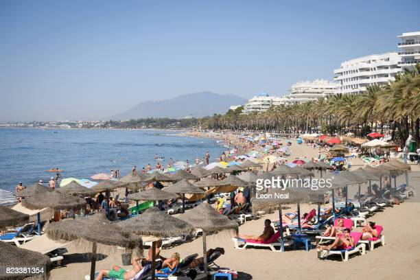 People lay on loungers and relax under umbrellas as they bask in the summer sunshine on the beach on July 24 2017 in Marbella Spain With Brexit...