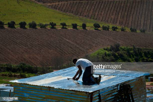 TOPSHOT People lay out plots and build shacks on a piece of land belonging to the Louiesenhof Wine Estate on August 8 in Stellenbosch which is at the...