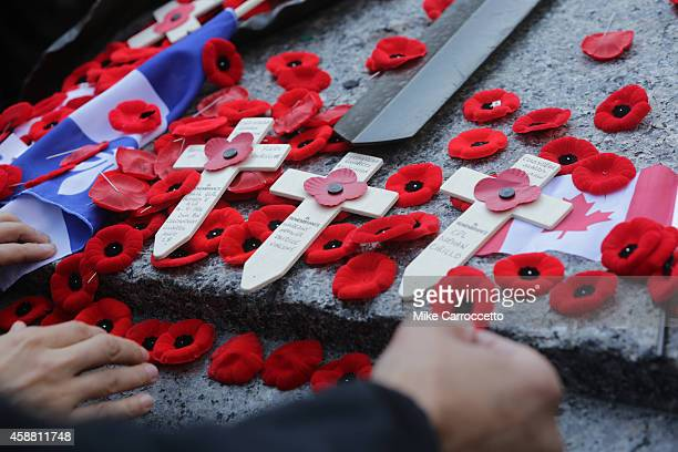 People lay poppies on the Tomb of the Unknown Soldier after this morning's Remembrance Day ceremony November 11 2014 in Ottawa Canada An estimated...