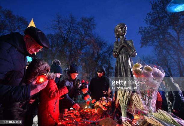 People lay symbolic sheaves of wheat and light candles during a commemoration ceremony at a monument to victims of the Holodomor famine of 193233 in...