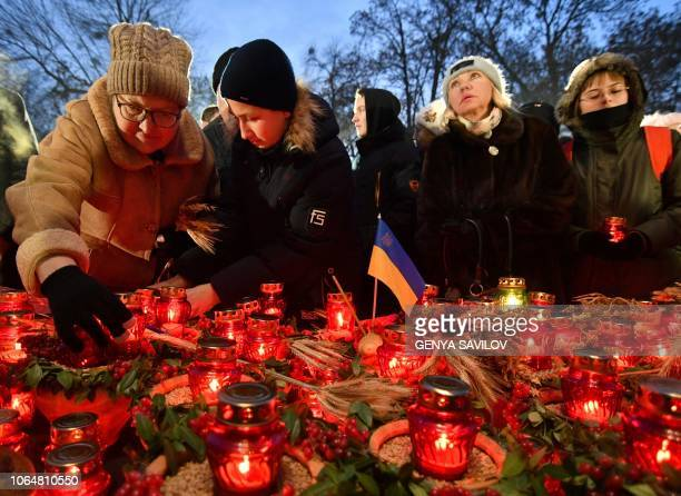 People lay symbolic sheaves of wheat and lit candles during a commemoration ceremony at a monument to victims of the Holodomor famine of 193233 in...