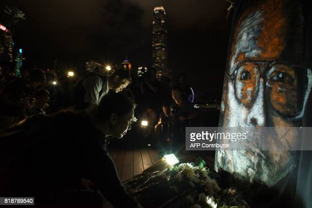 TOPSHOT People lay white flowers in front of a large portrait of the late Chinese Nobel laureate Liu Xiaobo in hong Kong on July 19 2017 Hundreds...