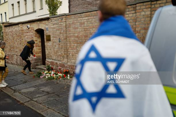 People lays flowers on October 10 2019 at the synagogue in Halle eastern Germany one day after the attack where two people were shot dead At least...