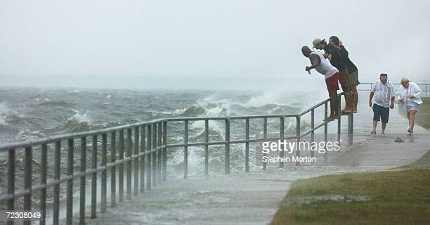 People lean into the wind and waves as the outer bands of Hurricane Ivan lash the pound Escambia Bay September 15 2004 Pensacola Florida High winds...