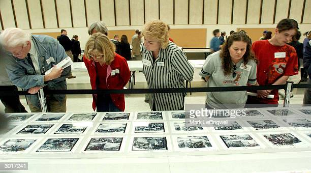 People lean over a barrier to get a closer look at photographic evidence at the Jefferson County Fairgrounds February 26 2004 in Golden Colorado The...