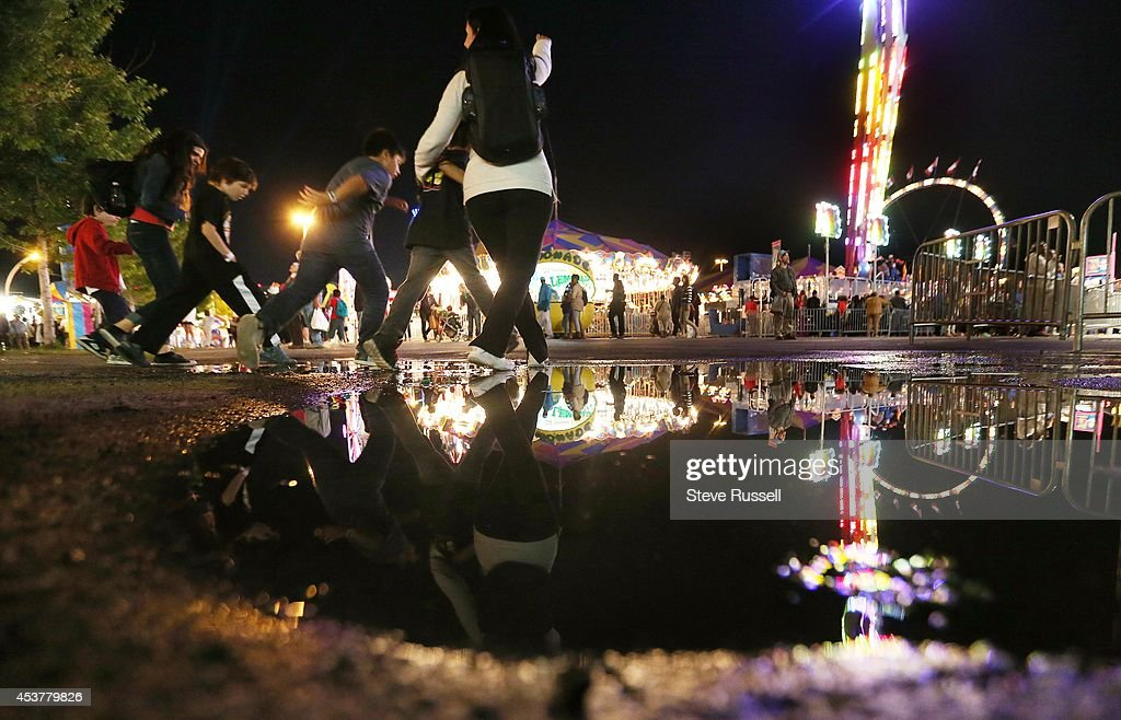 TORONTO, ON- AUGUST 15 - People leap over a puddle created by spray from the Niagara Falls ride as the sun sets on the first night of the Canadian National Exhibition. The Ex has been running for a total of 135 years. at CNE Grounds in Toronto. August 15, 2014. Steve Russell/Toronto Star