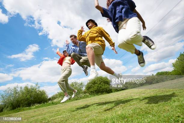 people leaping in the air on a summer's day - human limb stock pictures, royalty-free photos & images