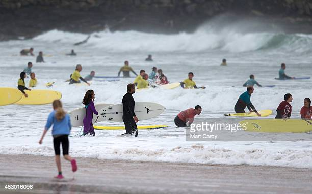 People learn to surf as a heat of the UK Pro Surf Association's Men's Open takes place nearby on Fistral Beach on the first day of the Boardmasters...