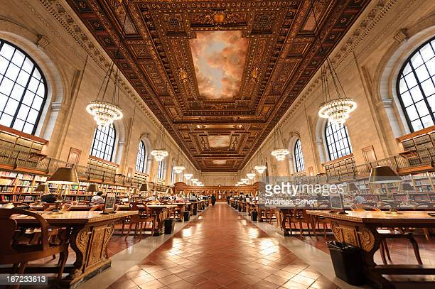 People learning on big tables in New York Public Library, wide angle indoor shot, lamps light up the room, quiet room