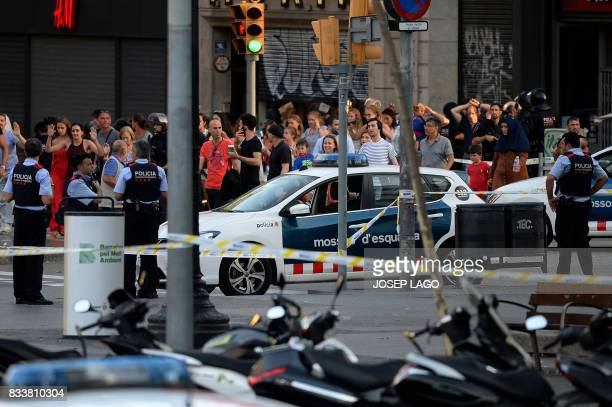 TOPSHOT People leave a fastfood with hands up as asked by policemen after a van ploughed into the crowd killing two persons and injuring several...