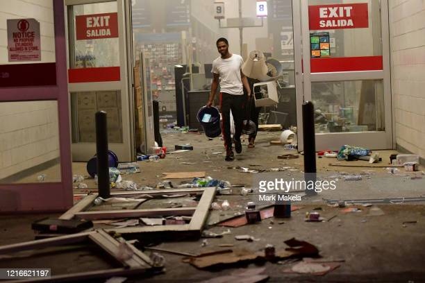 People leave a hardware store with merchandise during widespread unrest following the death of George Floyd on May 31 2020 in Philadelphia...