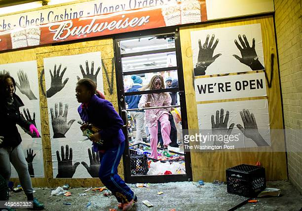 People leave a liquor store with items after protestors rioted following the grand jury announcement in the Michael Brown case on November 24 2014 in...