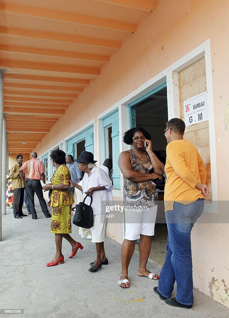 People leave a polling station after voting, on March 21, 2010, in Fort de France, in the French Caribbean island of Martinique, during the second round of the French regional elections. French voters came out today expected to deal French President a stinging rebuke in regional elections that will be his last big national test before seeking re-election in 2012.