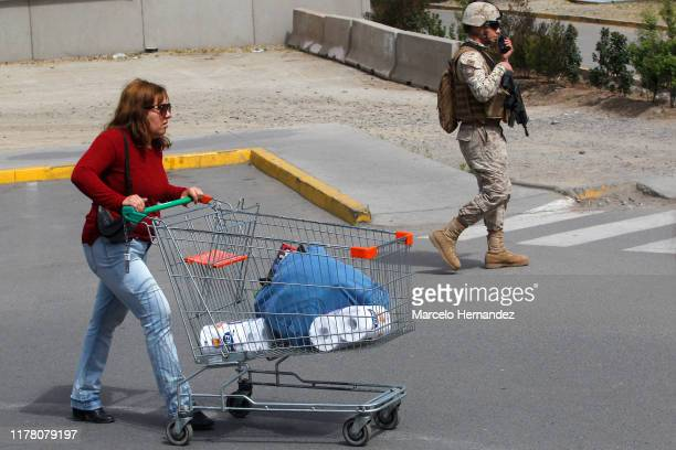 People leave a shop with their bags in supermarket of Puente Alto during the eighth day of protests against President Sebastian Piñera's government...