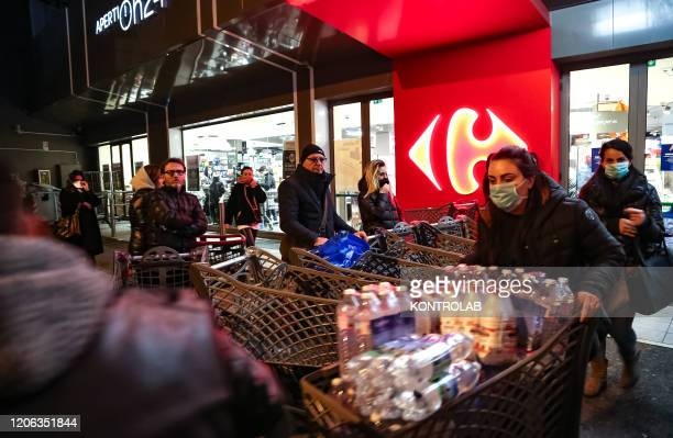 People leave a supermarket at night with supplies supplies after the government announced that the whole Italy will be declared emergency area to...