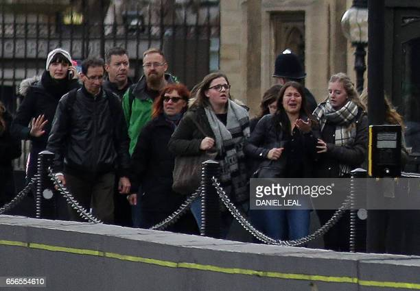 People leave after being evacuated from around the Houses of Parliament and Parliament Square in Westminster central London on March 22 2017 during...