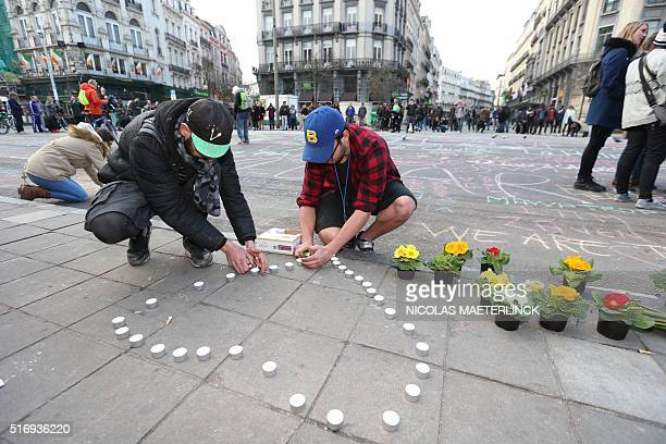 People leave candles and flowers in tribute to victims of triple bomb attacks in front of the stock exchange building in the city center of Brussels...