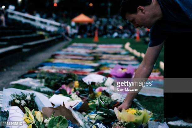 People leave flowers as they attend a vigil for the lives taken in the Christchurch terror attacks at the Auckland Domain on March 22 2019 in...