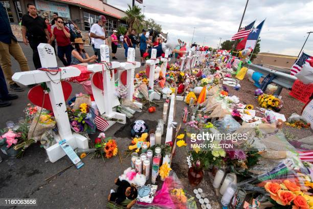 People leave flowers at a makeshift memorial for shooting victims at the Cielo Vista Mall Walmart, in El Paso, Texas, on August 6, 2019. - The August...