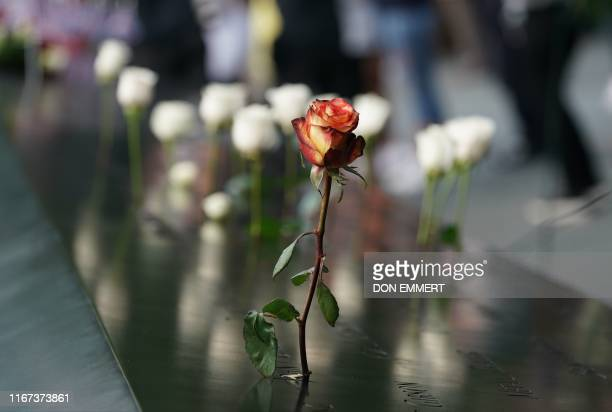 TOPSHOT People leave flowers during the September 11 Commemoration Ceremony at the 9/11 Memorial at the World Trade Center on September 11in New York