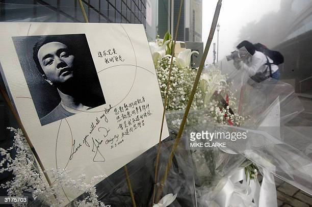 People leave flowers in memory of entertainer Leslie Cheung prior to queuing outside Madame Tussaud waxworks in Hong Kong for a viewing of the...