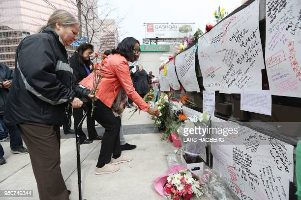 People leave flowers on April 24 at a makeshift memorial for victims of the van attack in Toronto A van driver who ran over 10 people when he plowed...