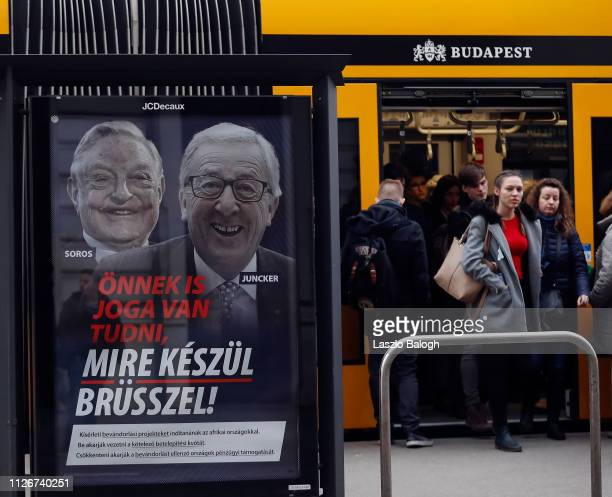People leave from the tram next to a billboard with portraits of European Commission chief JeanClaude Juncker and Hungarianborn US billioner George...