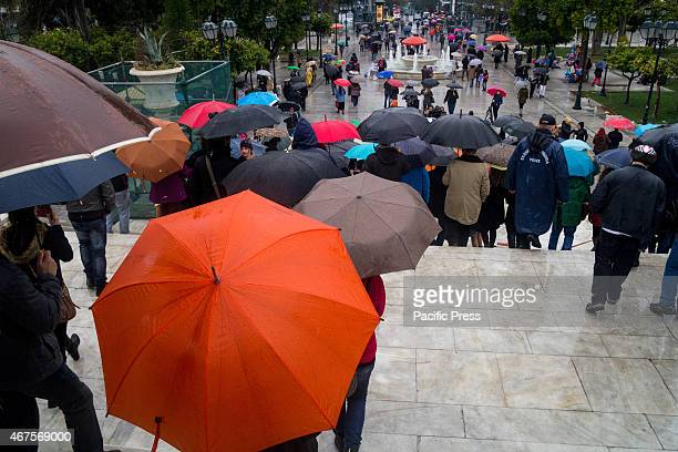 People leave holding umbrellas after the end of the parade The anniversary of Greece's liberation from Turkish occupation in 25th March 1821...