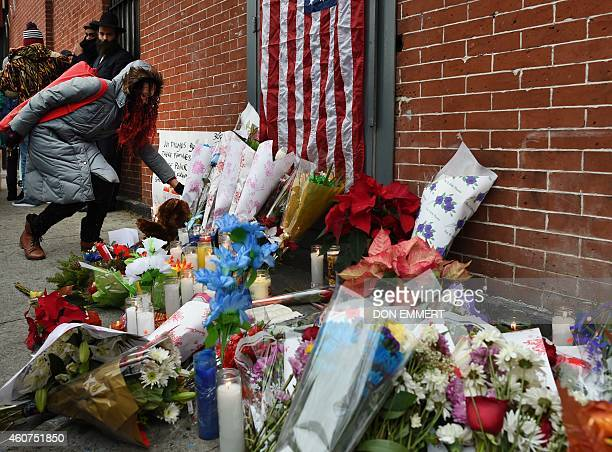 People leave items at a memorial near Tompkins Ave and Myrtle Ave December 21 2014 in New York near the site where two New York City police officers...