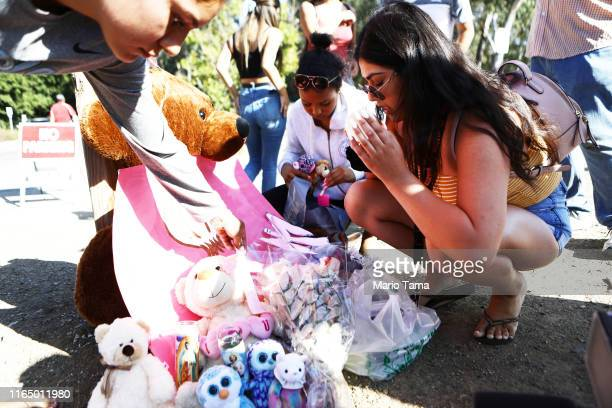 People leave mementos at a makeshift memorial outside the site of the Gilroy Garlic Festival after a mass shooting took place at the event yesterday...